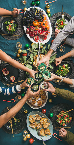 Company of friends gathering for Christmas or New Year party dinner at festive table. Flat-lay of hands holding glasses with drinks, feasting and celebrating holiday, top view, vertical composition