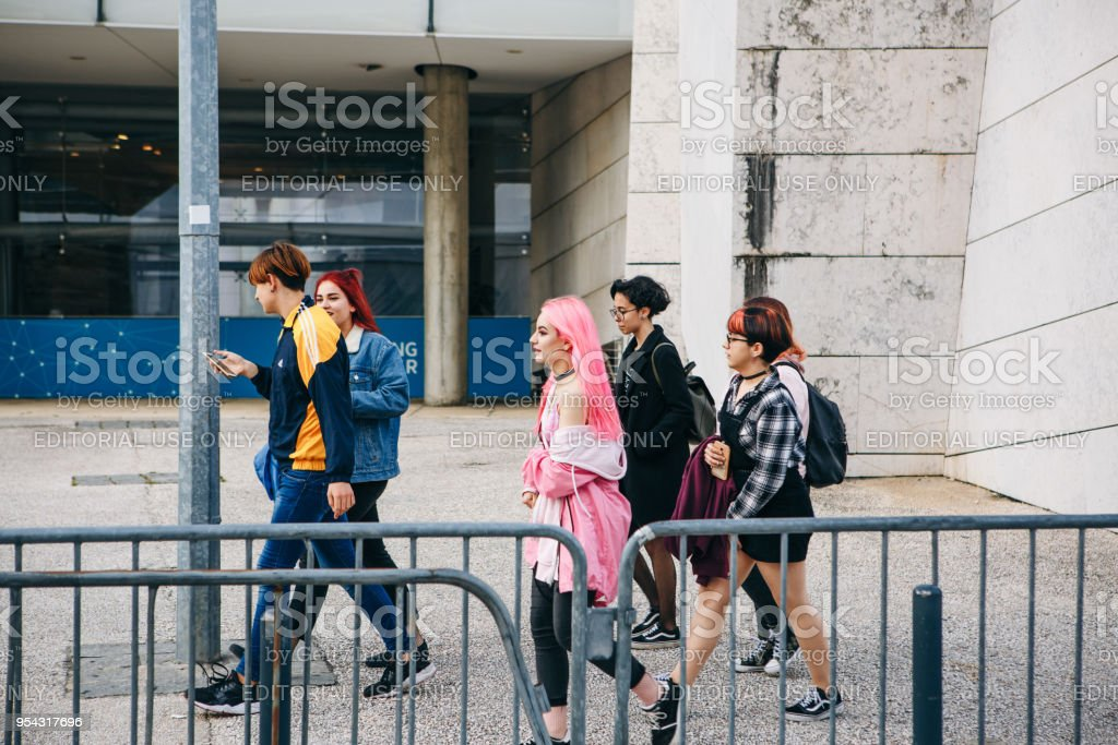 Company of friends or group of people or kids or teenagers walk down by street stock photo