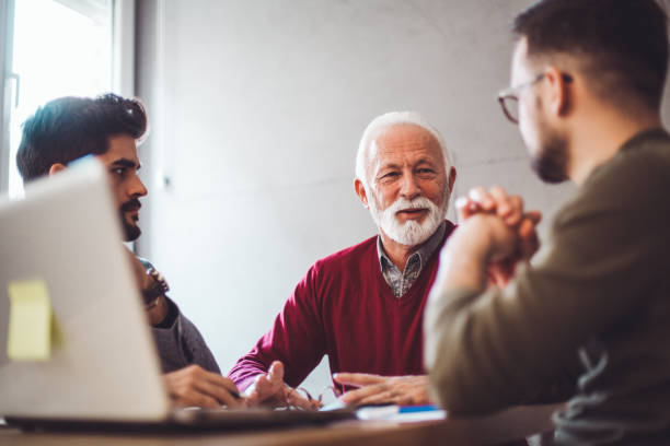 Company owner on a meeting with two of his employees in his office. stock photo