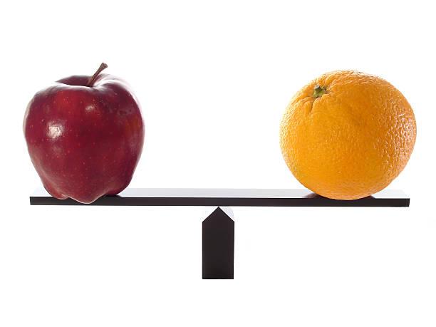 Compare Apples to Oranges Balanced stock photo