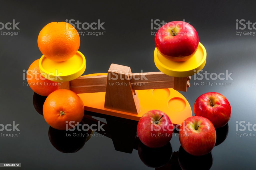 Comparing apples to oranges concept stock photo
