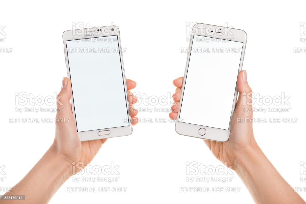 Comparing iPhone 6 Plus and Samsung Galaxy Note 4 displaying white stock photo