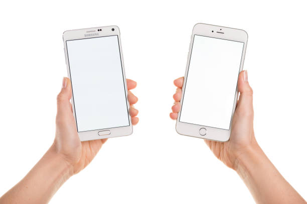 comparing iphone 6 plus and samsung galaxy note 4 displaying white - human hand stock photos and pictures