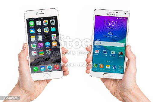 Koszalin, Poland - Jun 01, 2015: Close-up shot of white iPhone 6 Plus and white Samsung Galaxy Note 4 hand-held by woman. IPhone 6 Plus (5.5 inches) is biggest smartphone from Apple. Samsung Galaxy Note 4 is his competitor from Samsung. Devices displaying the applications on the home screen.