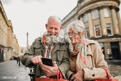 Senior couple standing out on a city street as they hold bags from their Christmas shopping. They are holding a smart phone as they compare prices online.