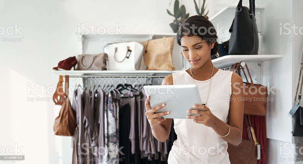 Comparing prices with her handy tablet stock photo