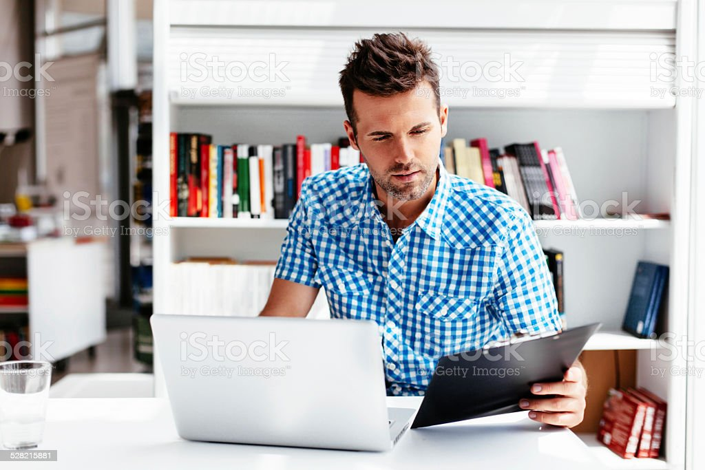 Comparing the answers Male student studying in the university library Adult Stock Photo