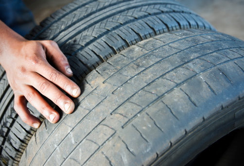 A photograph comparing a dangerously worn tire beside a newer tire with acceptable tread.