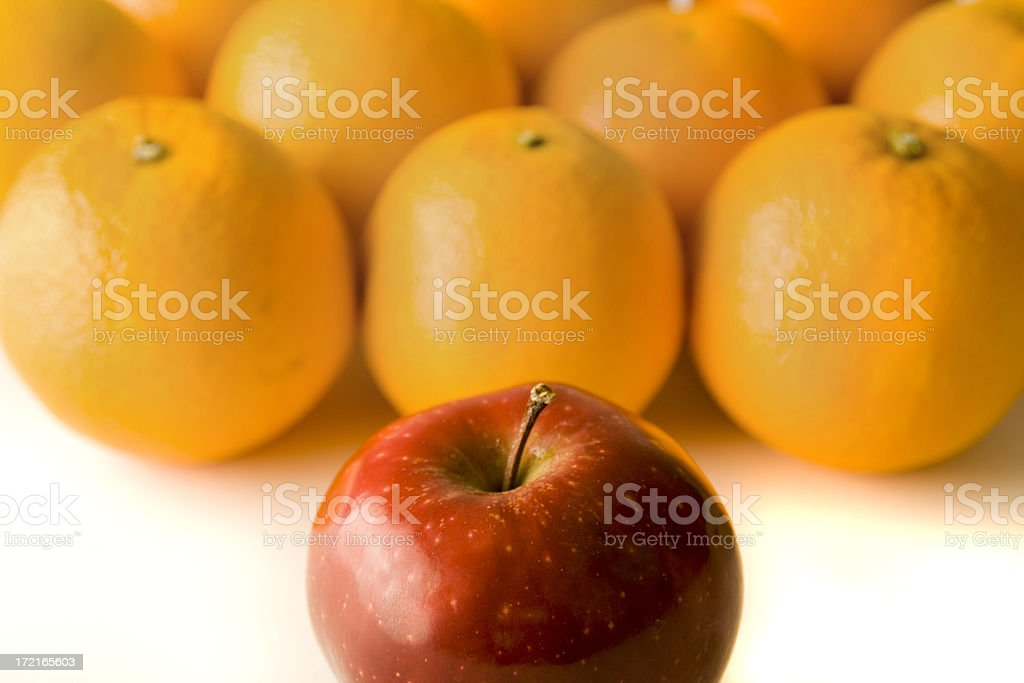 Comparisons—Individual Apple Standing out from the Crowd of Oranges stock photo