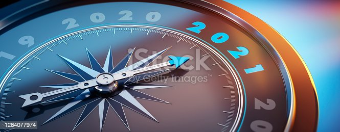 Dark stylish compass with needle pointing to the year 2021