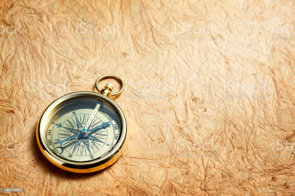 Compass against a brown bumpy background stock photo