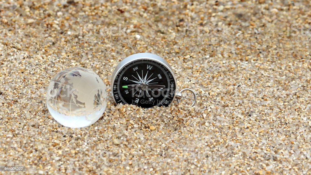 A compass and a mini globe on the sand. stock photo