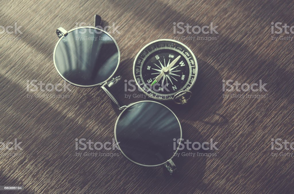 compass and glasses on wood table desk royalty-free stock photo