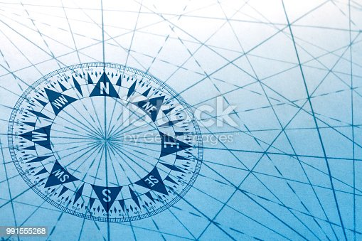 A compass and the navigational lines from an old map. A cool blue cast dominates the scene.