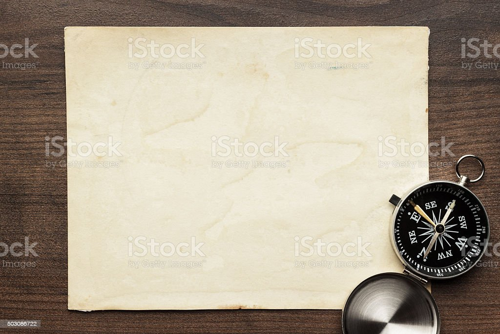 compass and old paper on the brown wooden table stock photo
