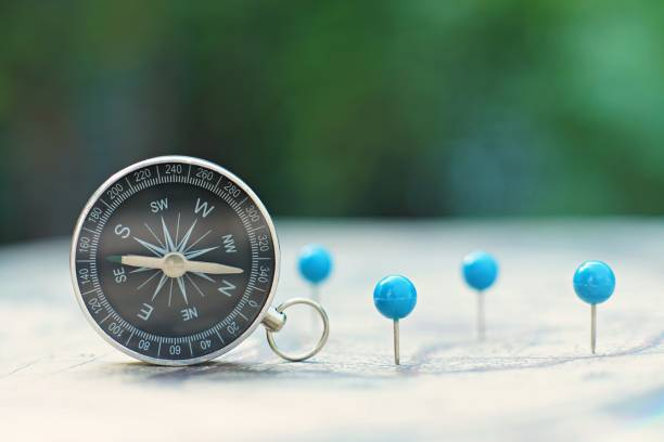 Compass and pin point marking with vintage world map background Compass and pin point marking with vintage world map background straight pin stock pictures, royalty-free photos & images