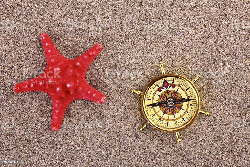 Bússola e estrelas do mar em uma praia de areia - foto de acervo