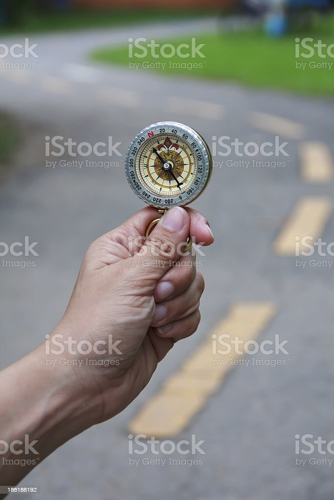 Compass being held out to determine direction royalty-free stock photo