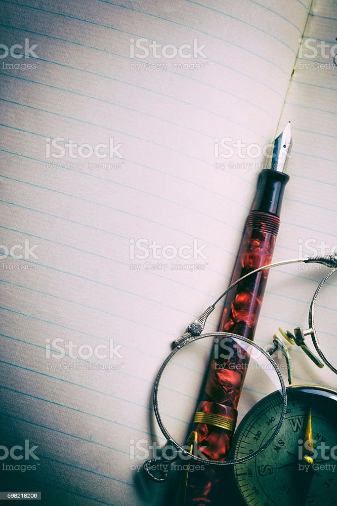 Compass Fountain Pen And Spectacles On Notebook foto royalty-free
