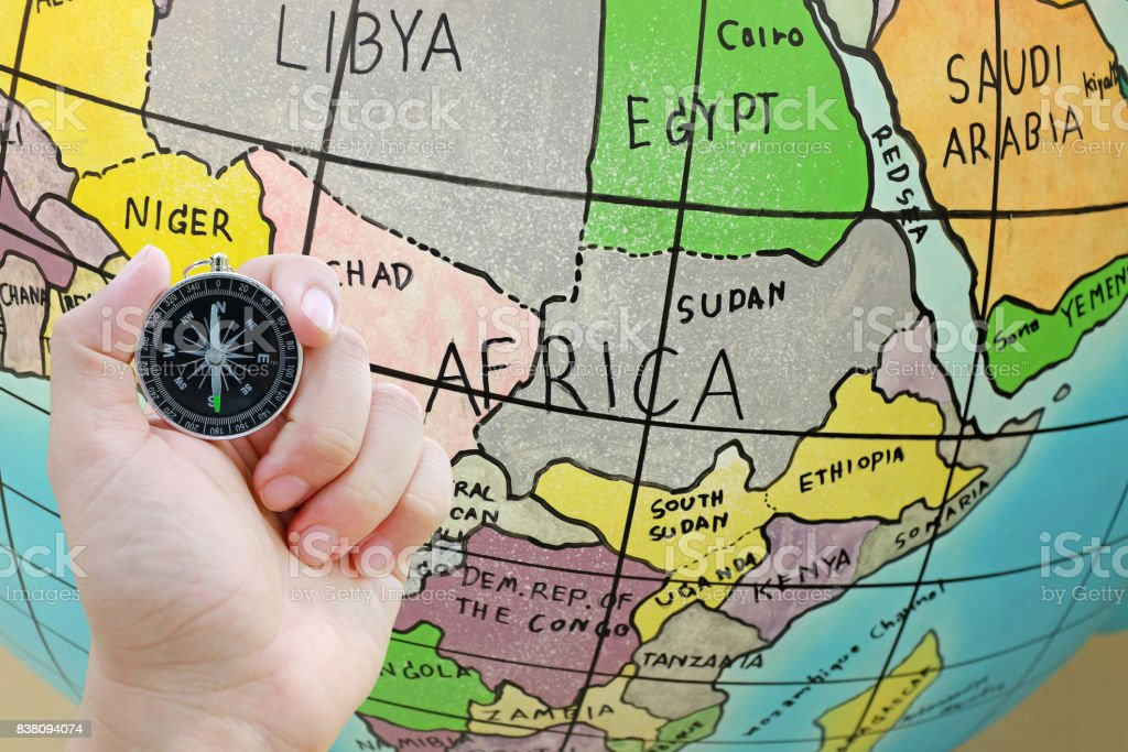 Compass in hand against globe map background. stock photo