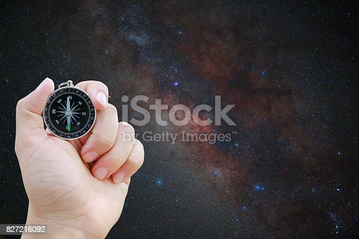 1008093204 istock photo Compass in hand against Universe space milky way galaxy with many stars at night. 827216092