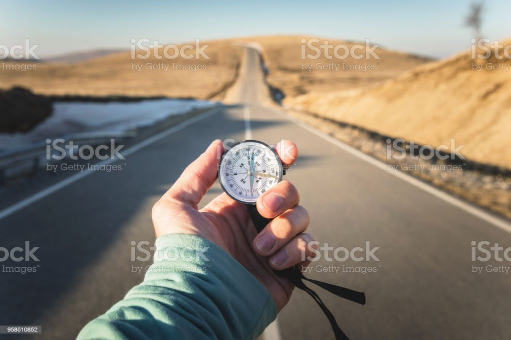 Compass in Hand mountain road background .Vintage Tone royalty-free stock photo