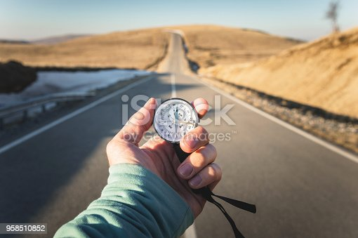 Compass in Hand mountain road background .Vintage Tone.