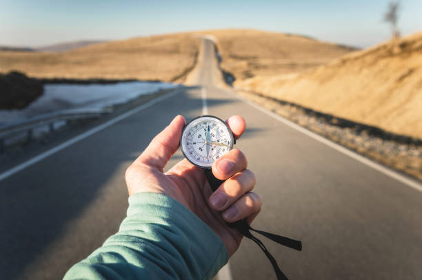 compass in hand mountain road background .vintage tone - west direction stock pictures, royalty-free photos & images