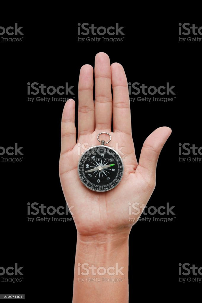 Compass in hand on a black background close-up. stock photo