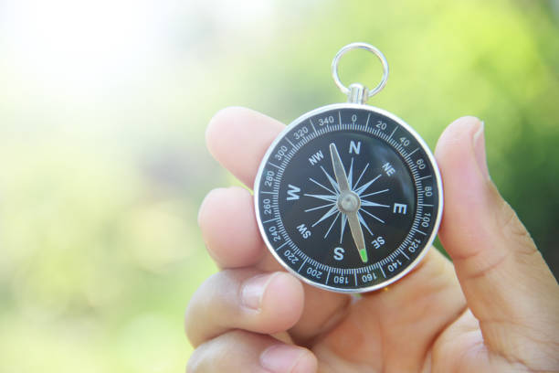 compass in hand outdoors - navigational compass stock photos and pictures