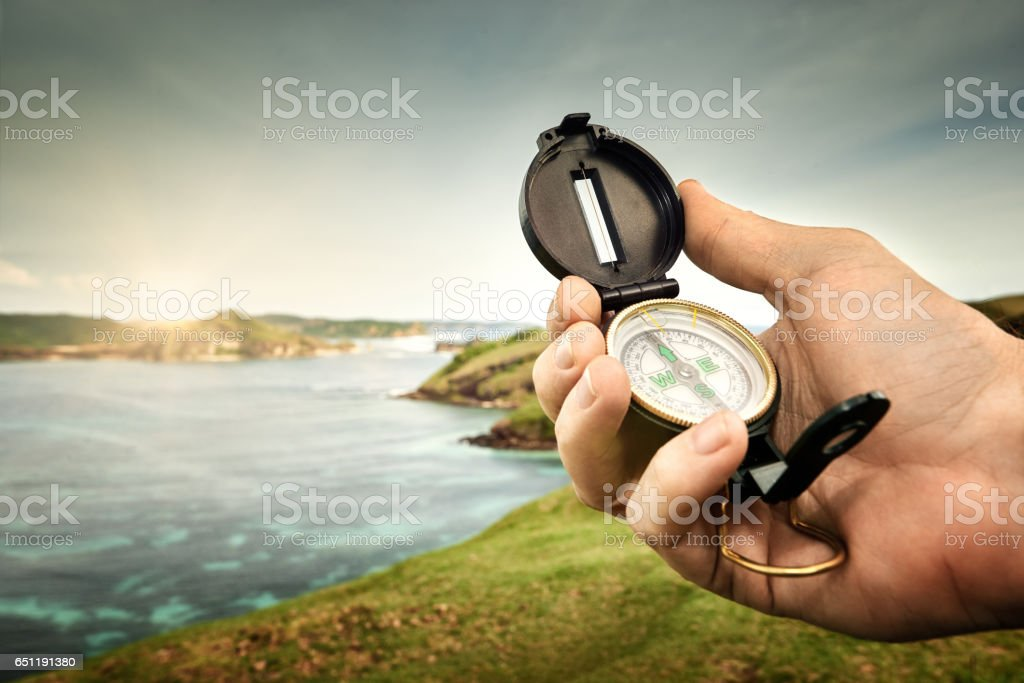 Compass in hand traveler on coastline near ocean on background hills and mountains. stock photo
