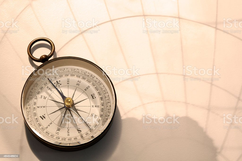 Compass In Shadow Cast By Transparent Globe stock photo