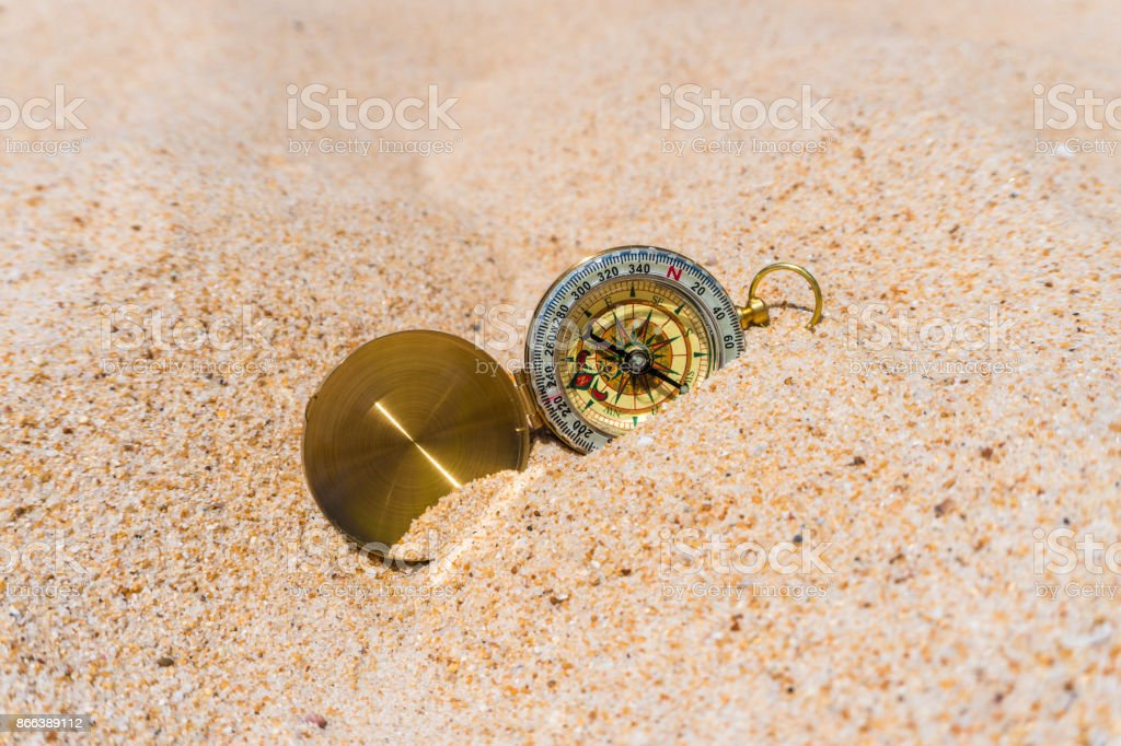 Compass in the gold sand on the beach. Summer time stock photo