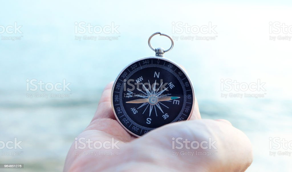 Compass in the hand with sea background. royalty-free stock photo