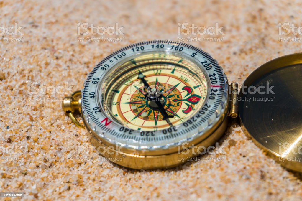 Compass in the sand on the beach. summer time stock photo