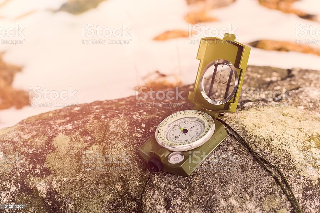 Compass instrument on rock stock photo