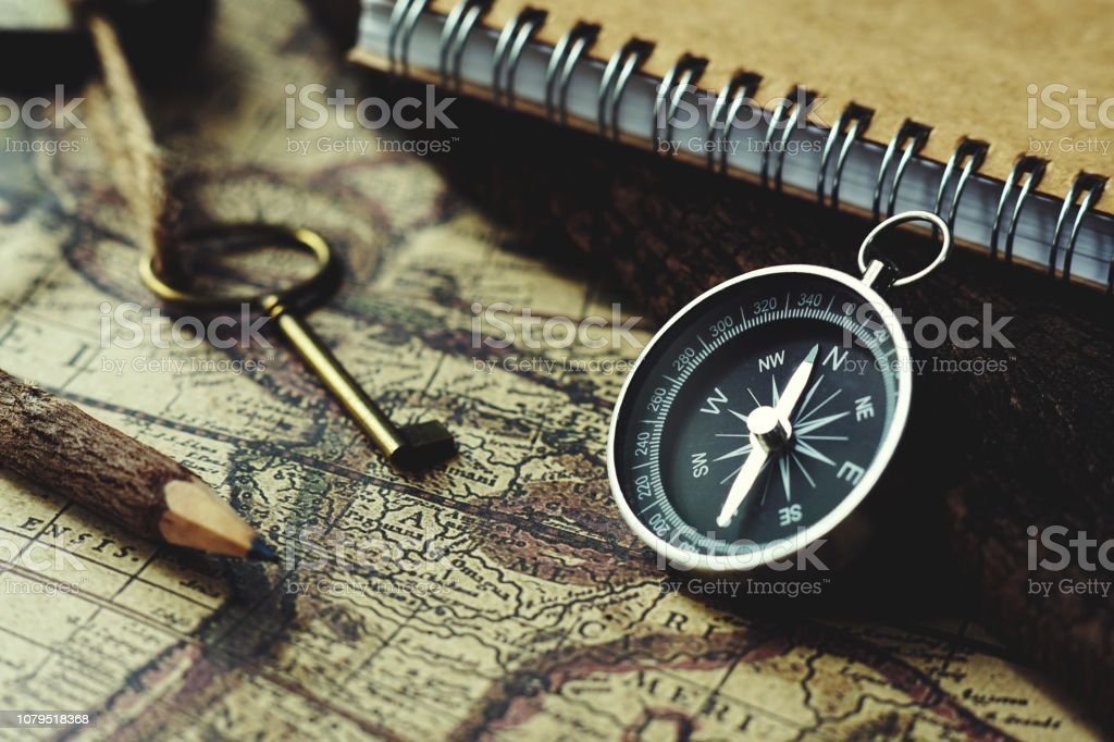 Compass, key, pencil and book on blur vintage map background, retro classic color tone stock photo