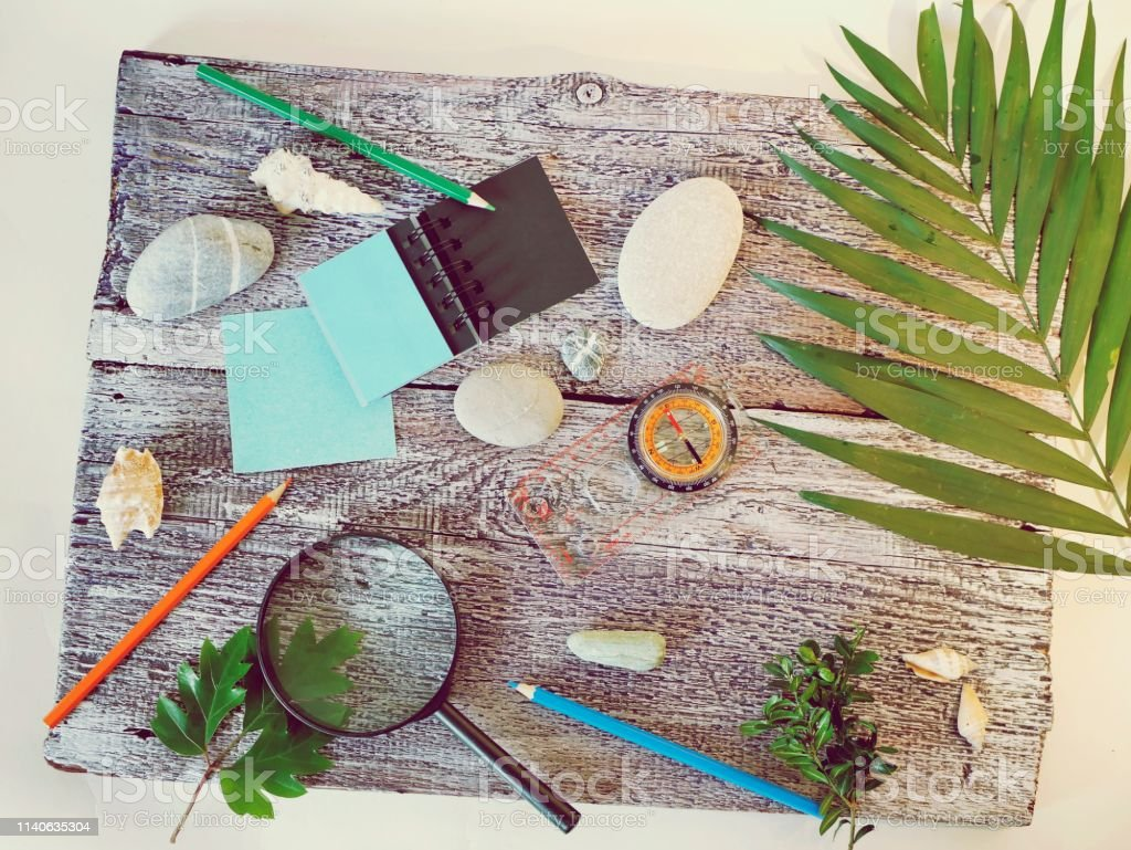 Compass, magnifier, notepad, pencil, sea stones on a textural wooden...