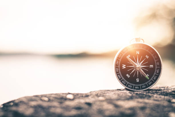 Compass of tourists on mountain at sunset sky. stock photo
