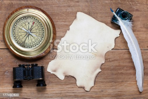 istock Compass, old paper, binoculars, quill and inkwell on wood 177492800
