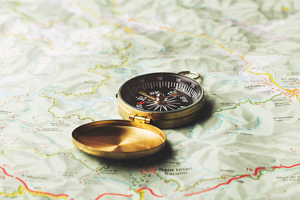 compass on a map background - kompass wanderkarte stock-fotos und bilder