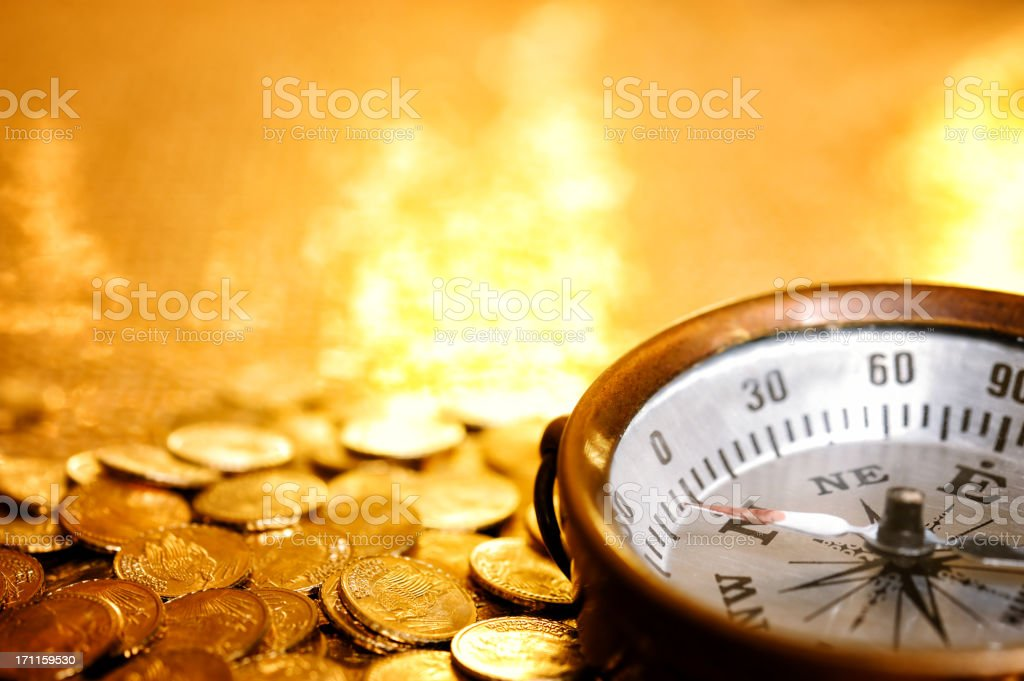 Compass on gold coins stock photo