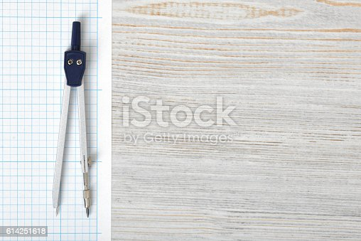 613651130 istock photo Compass on graph paper in top view with copy space 614251618