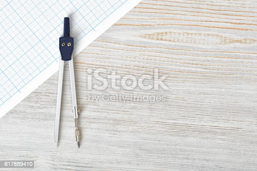 613651130 istock photo Compass on graph paper in top view with copy space 617889410