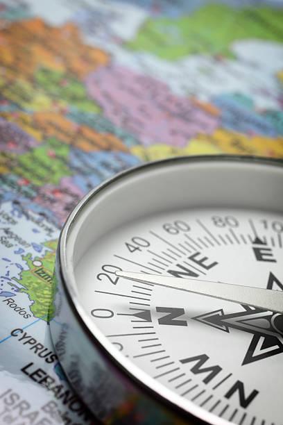 kompass auf einer karte - kompass wanderkarte stock-fotos und bilder