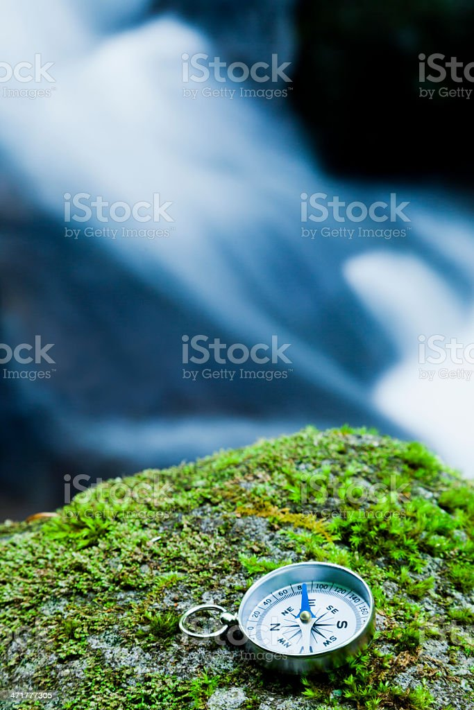 Compass on mossy rock royalty-free stock photo