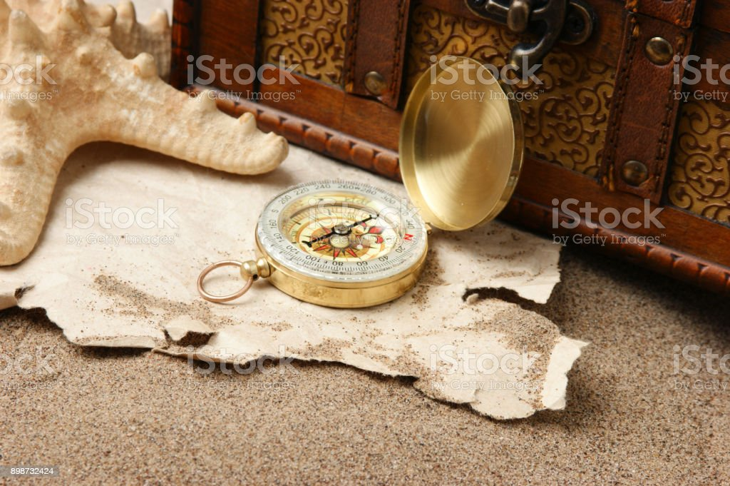 Compass on old sheet paper against the background of sand stock photo