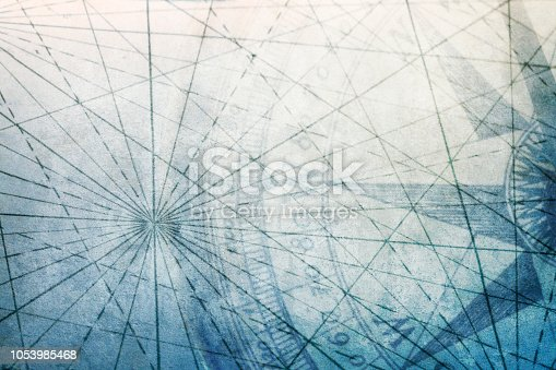 A compass and the converging navigational lines from an old world map on a textured background.