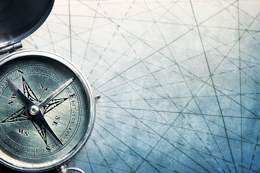 A close up of a compass as it rests on the converging navigational lines of an old map.