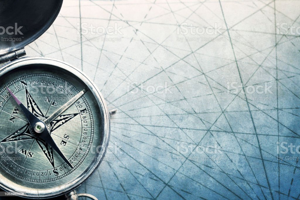 Compass On Old World Map With Navigational Lines On Textured Surface stock photo